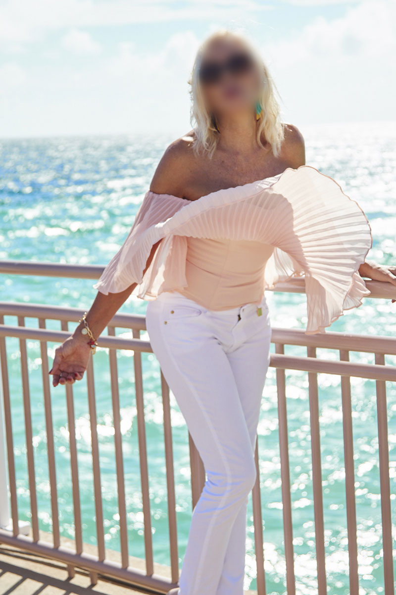 blonde on balcony overlooking miami beach
